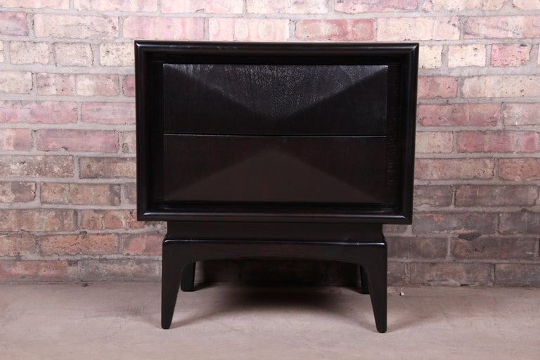 A stunning Mid-Century Modern diamond front nightstand  In the manner of Vladimir Kagan  By United Furniture Co.  USA, 1960s  Ebonized walnut, with unique sculpted diamond front design.  Measures: 23