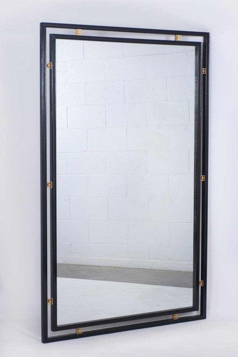 This vintage midcentury wall mirror is in great condition, comes with its original mirror glass that's fully reflective, has a new ebonized lacquered finish, and comes with decorative brass accents around the mirror. This 1960 ebonized floor mirror