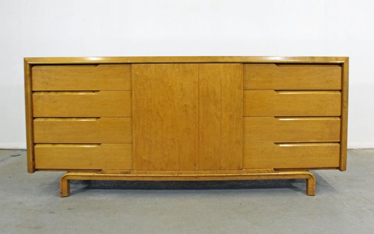 Offered is a beautiful vintage midcentury credenza designed by American designer Edmond J. Spence. Has ample storage space with four dovetailed drawers on each side and a middle door with one drawer and space for storage inside. One top drawer has