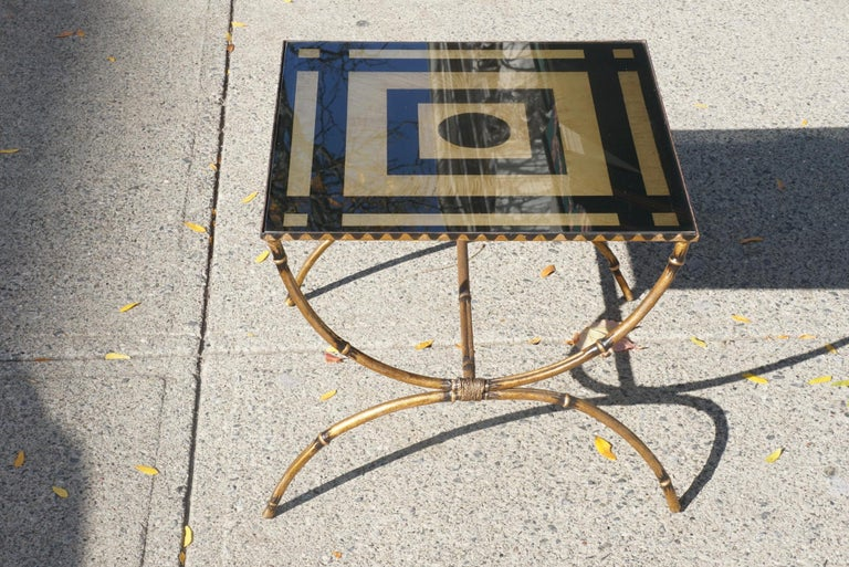 Made in America circa 1955 this low wrought iron table is made to resemble bamboo and is then gilded and painted with a wavy decorative border along the apron. Set within the frame of the apron is a reverse glass painted and gilded top. The design