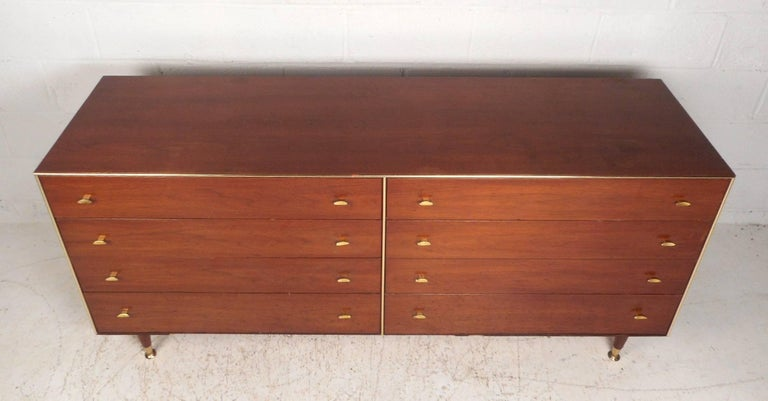 This stunning vintage modern dresser features eight large drawers with sculpted brass pulls on each. A unique design with brass trim running along the edges of the front and brass feet. Quality construction by R-Way with tapered legs and a beautiful
