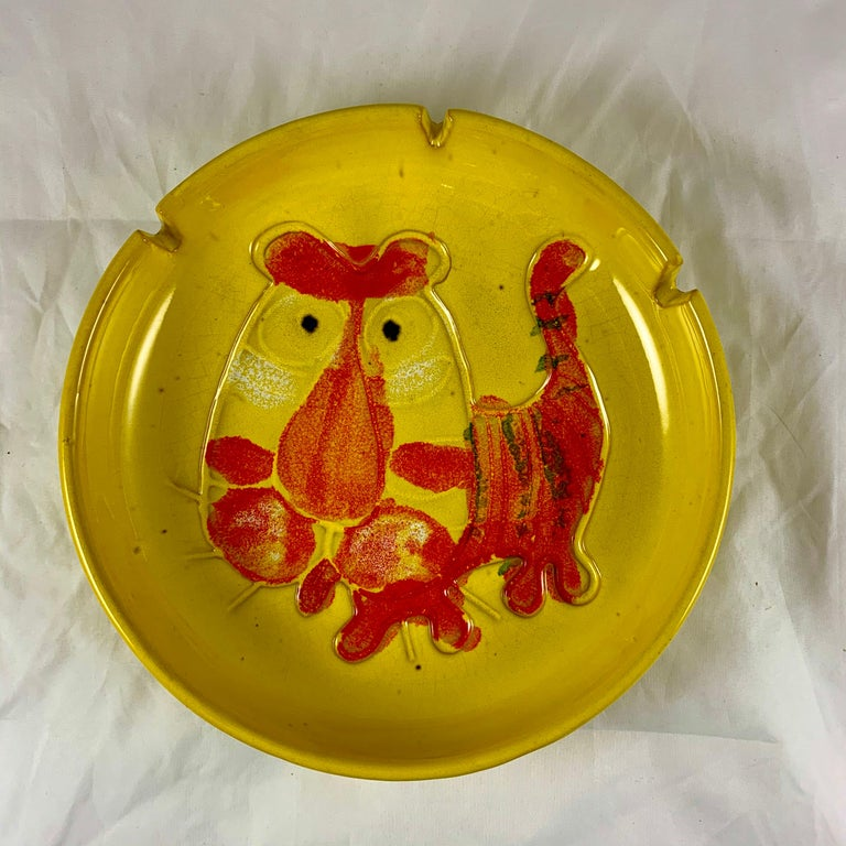 An oversized midcentury Tiger ashtray, signed B. Walsh (Bennett Walsh), dated 1973.  Made of stoneware and showing an incised image of a tiger glazed in primary pop-colors of orange on yellow. The deep rim has three slots for holding cigarettes. A
