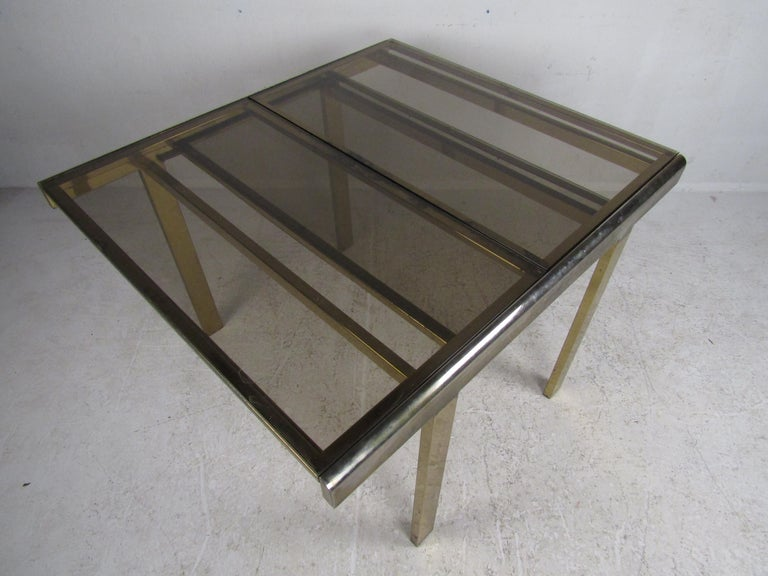 This vintage eye-catching Mastercraft style brass adjustable table with beautiful smoked/tinted glass conveniently expands to accommodate guests. Easily slides open to the length of 66