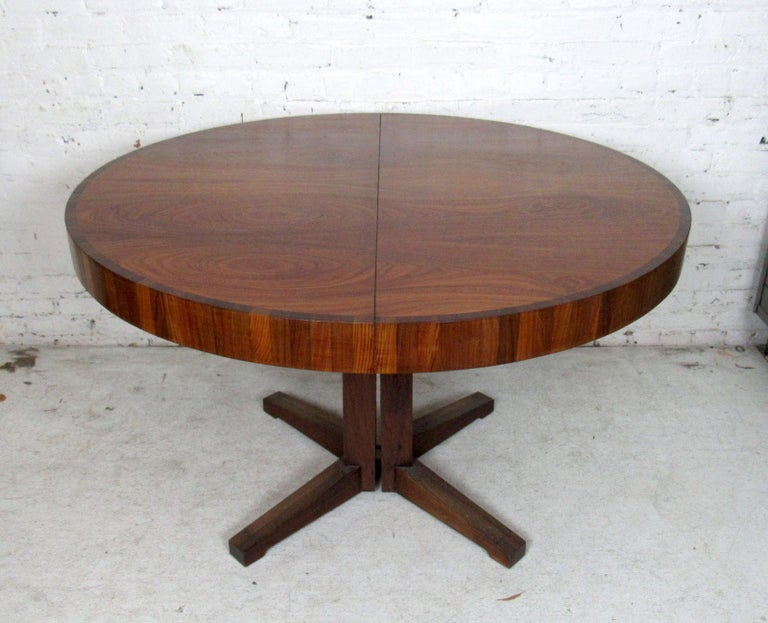 Vintage modern round dining table featured in rich rosewood grain. This dining table comes with a leaf that extends the length of the table into an oval shape.