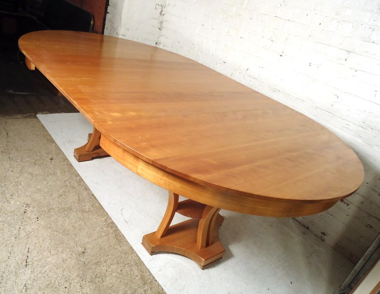 Gorgeous vintage modern extendable table extends from round to oval featuring two wood leaves. Open width: 85