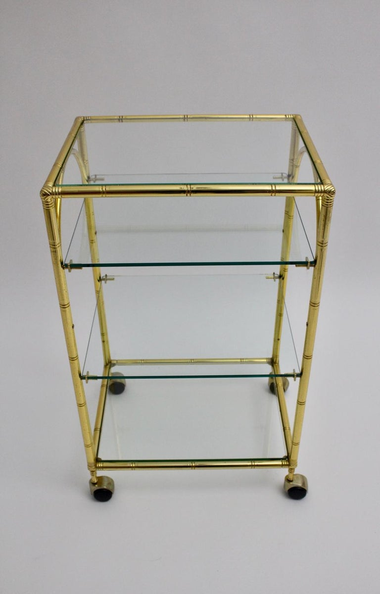 This presented gilded faux bamboo bar cart attributed to Maison Baguès France 1960s features four glass plates and four wheels. The glass plates have no chips or damages. The condition is very good with minor signs of age.