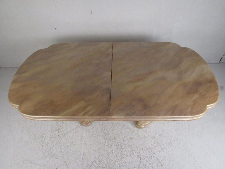 This stunning vintage modern dining table features a sculpted top, double pedestal base and metal trim along the smooth edges. Exquisite detail and a faux finish adds style and grace to any modern interior. Please confirm item location (NY or NJ).