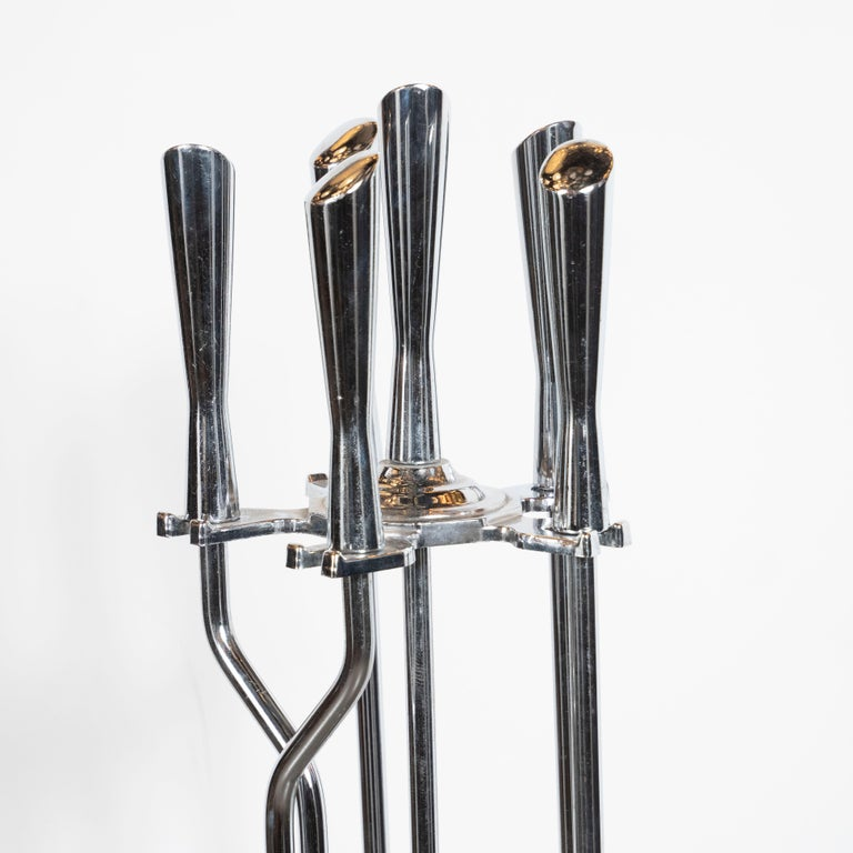 This refined Mid-Century Modern fireplace tool was realized in the United States, circa 1960. The set includes stand, shovel, brush, tongs and poker created in lustrous polished chrome with abstracted hour glass form handles in the same material.