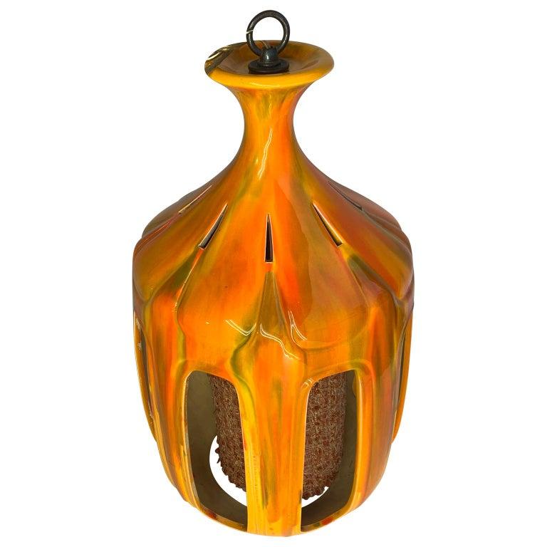 Mid-Century Modern flaming orange ceramic pendant.
