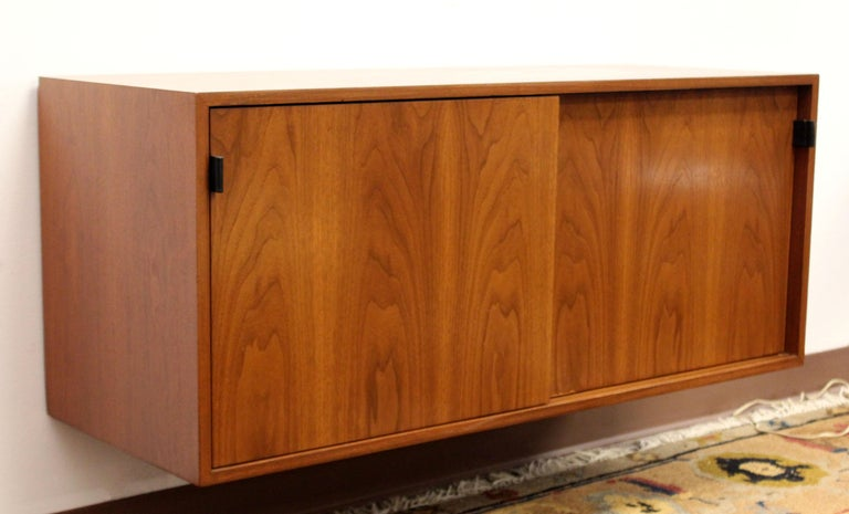 For your consideration is a fabulous rare vintage hanging floating wall unit cabinet, with sliding doors, made of walnut, by Florence Knoll, circa the 1960s. In excellent condition. The dimensions are 48