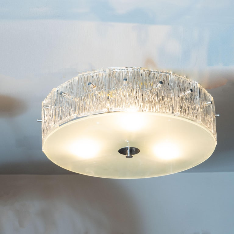 This elegant Mid-Century Modern chandelier was realized by the esteemed Mid-Century Modern maker, Kinkeldey, in Germany, circa 1960. It features a volumetric circular body with an abundance of rectangular glass shades- each with an organic texture