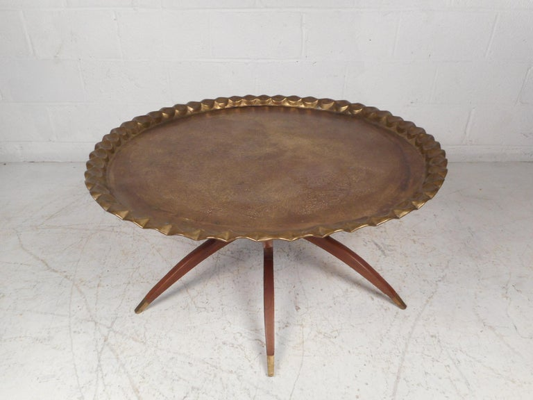 Very unusual midcentury cocktail table with a collapsing/folding base, and a large brass tabletop. Each wooden section of the base showcases an interesting sculpted profile with brass sabots at their feet, offering a nice continuity throughout the