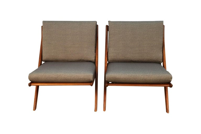 An absolutely stunning rare pair of Mid-Century Modern teak scissor lounge chairs by renowned Swedish designer Folke Ohlsson for Dux of Sweden, circa 1960s. Featuring beautiful teak wood frames with fabulous grain and detached cushions in new grey