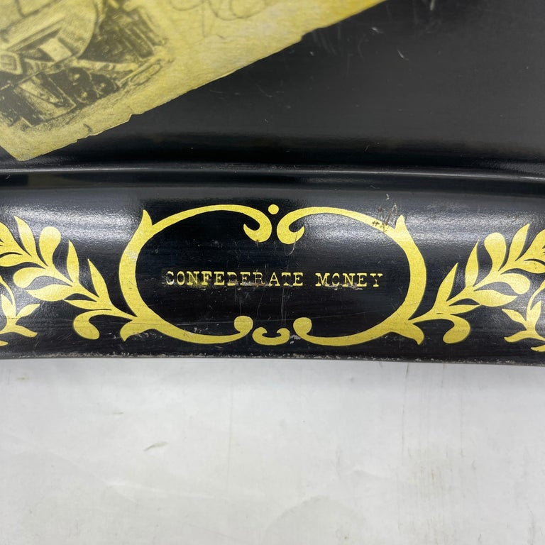 Painted metal tray with scalloped edges bearing the confederate money notes of early America. This mid-size serving tray is perfect for serving your guests. The painted gold trim and confederate money is bold and fun. In very good condition, a