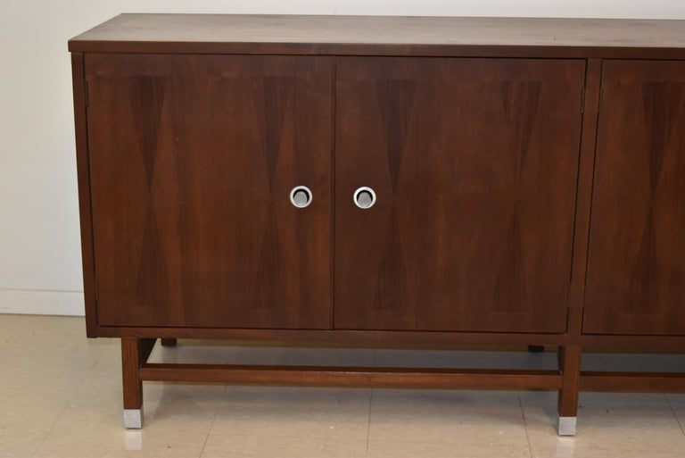Mid-Century Modern walnut four-door credenza by Stanley. Aluminum pulls and leg end caps. Adjustable shelves with drawers. ap20110.