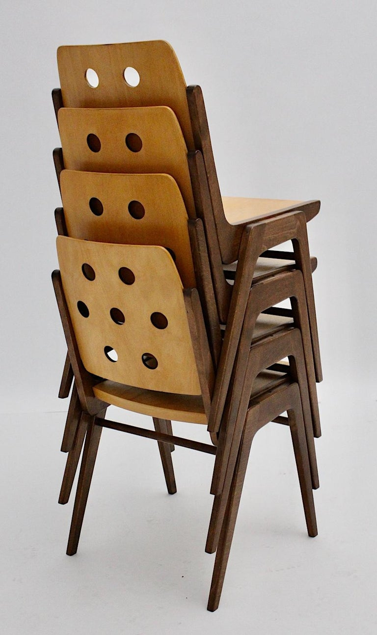 A set of 4 vintage stackable dining chairs, which were designed by the popular Viennese architect and furniture designer Franz Schuster and executed by Wiesner Hager. The frame was made of brown stained and natural lacquered solid beech while the