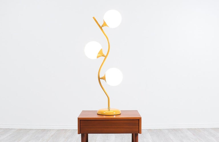 Vintage modern table lamp designed and made in the United States, circa 1960s. Our unique lamp features a mustard lacquered tulip base and stem that holds its glass globes that light up individually or together at the same time. Its organic and
