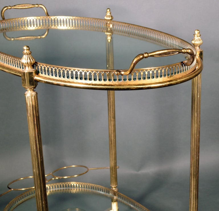 Mid-Century Modern French brass and glass bar cart The 1950s.   The oval Mid-Century Modern gold brass metal bar cart has two glass shelves with a pierced brass gallery. The top shelf is actually a tray which is a removable serving tray with