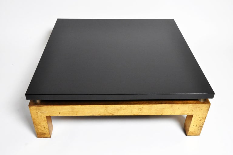 This handsome Mid-Century Modern coffee table is from France and is made from wood and lacquer. The piece features gold legs and a black lacquered top.