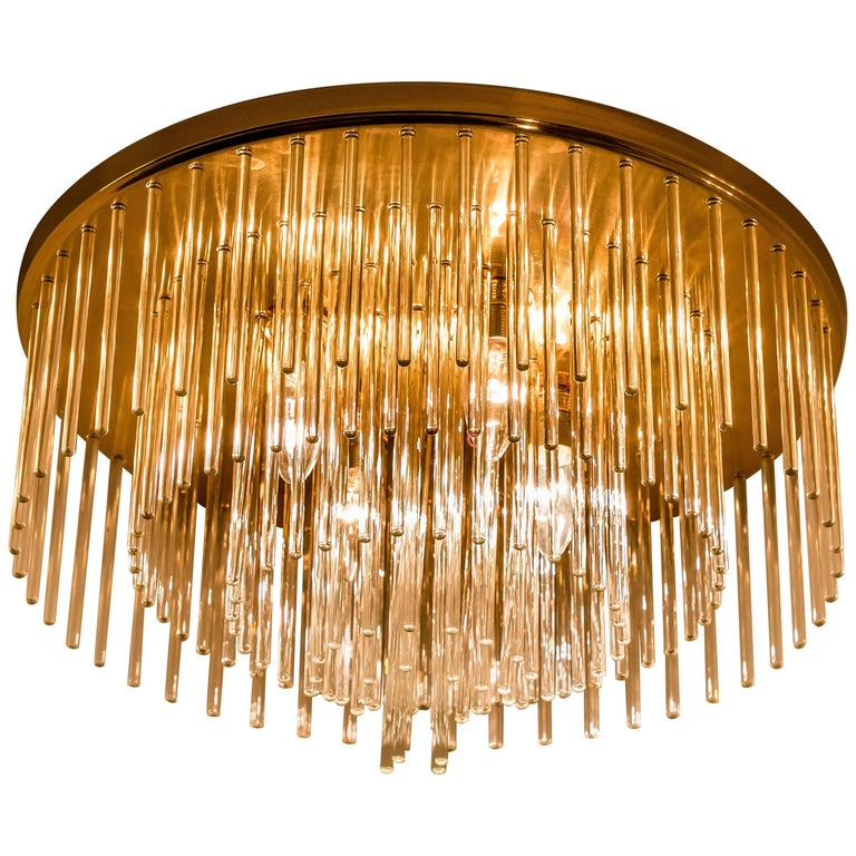 Clean lines to complement all decors. Wonderful high-end light fixture for Lightolier. With brass detail and hanging waterfall glass giving the piece an elegant appearance which refracts the light, filling a room with a soft, warm glow  The