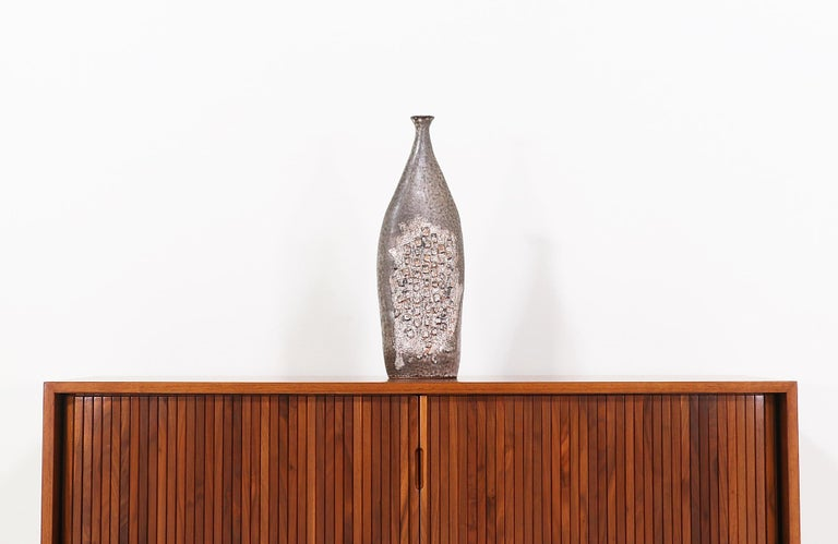 Unique Mid-Century Modern ceramic vase designed and manufactured in the United States in 1958. This biomorphic vase features a tall glazed ceramic body in earthy tones with a rich combination of textures and cubist detailing in the front and back.