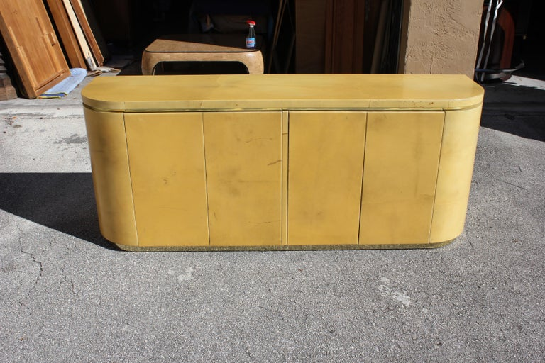 Beautiful goatskin sideboard or credenza, with beautiful grain detail in the goatskin hides, in the style of Karl Springer and Steve Chase, circa 1970s. Four doors open to reveal two drawers with shelves below. Ample storage space. Sitting on top