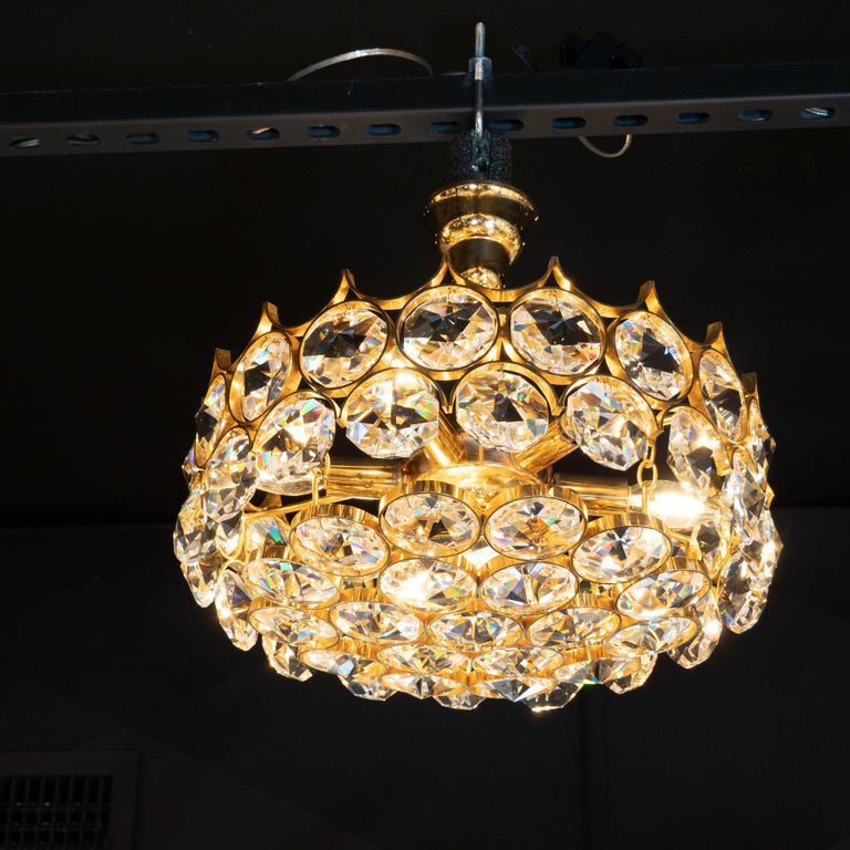 This exquisite Mid-Century Modern chandelier was realized by the illustrious maker Bakalowits & Sohne, circa 1960. It features two tiers of faceted circular crystals- that appear like diamonds- set into circular gold plated brass supports,