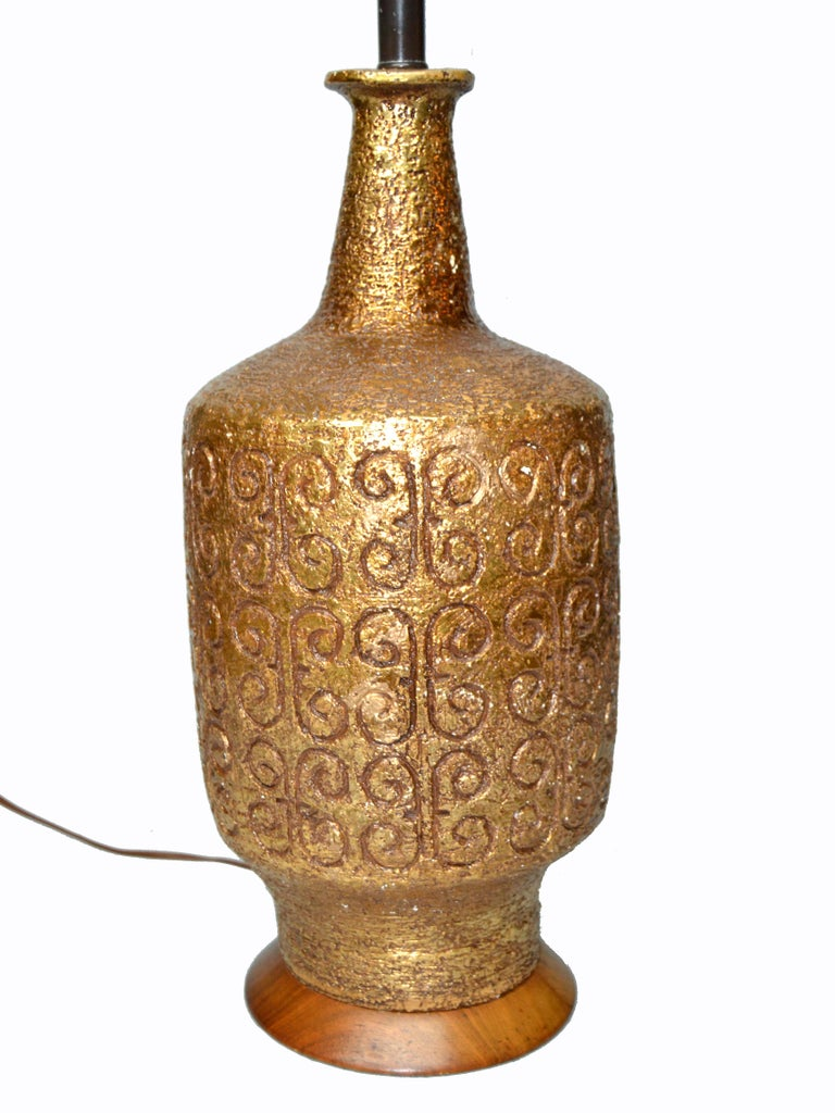 American Mid-Century Modern golden greek key pattern ceramic table lamp wood walnut base. Wired for the U.S. and uses a 3-way light bulb.