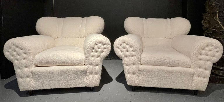 Italian Guglielmo Ulrich style lounge chairs. A fine pair from Italy circa 1940s. Upholstered in a plush Sherpa style fabric with painted wood. Unsigned. Sleek and stylish are these oversized pair of lounge chairs with tufted armrest fronts.