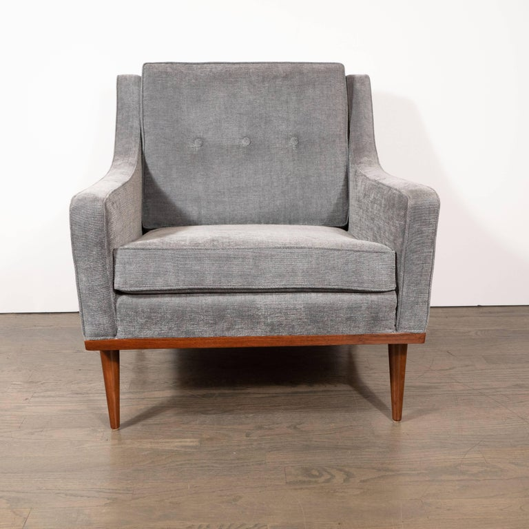 This elegant and understated armchair was realized in the United States, circa 1950. It offers a gently reclined back with three button details and curvilinear arms that curve upwards where they meet the angled back support. It sits on hand rubbed