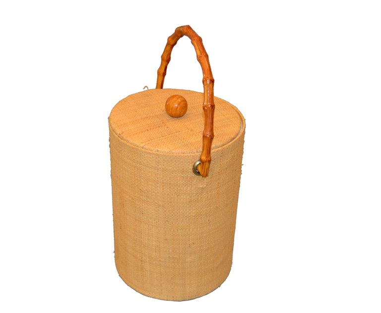 Mid-Century Modern insulated American made ice bucket with lid.  It is made with elegant woven cane wrapping bands and has an insulated wall and comes with a fitting lid. The handle and knob are made out of Bamboo. It is perfect for cooling wine,