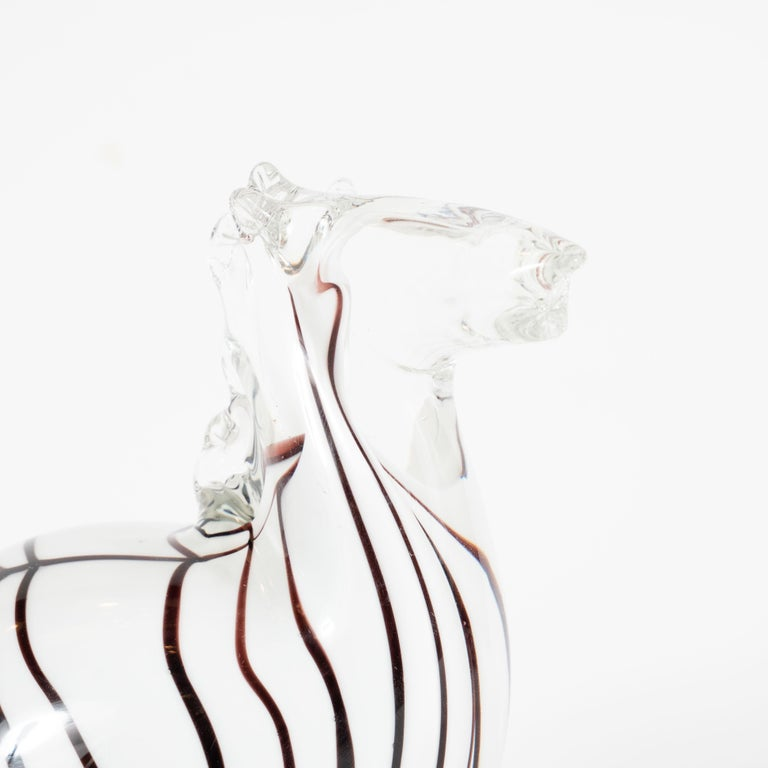 This whimsical, yet refined, Mid-Century Modern decorative object in the form of a stylized zebra was realized in Murano, Italy- the island off the coast of Venice renowned for centuries for its superlative glass production, circa 1960. It presents