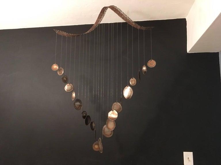 Twenty-four discs hanging from a spiral, true midcentury sculpture.