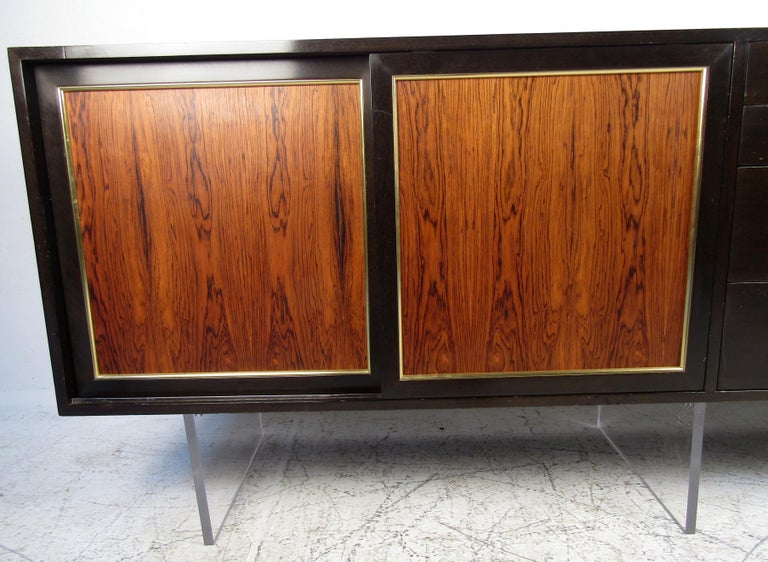 Vintage modern hutch featured in rich rosewood grain, Lucite base, four drawers, spacious storage space, and brass trimming.   Please confirm the item location (NY or NJ).