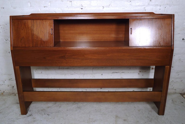 Vintage modern headboard featured in rich walnut grain, two sliding doors with storage space, and a middle storage compartment.  (Please confirm item location - NY or NJ - with dealer).