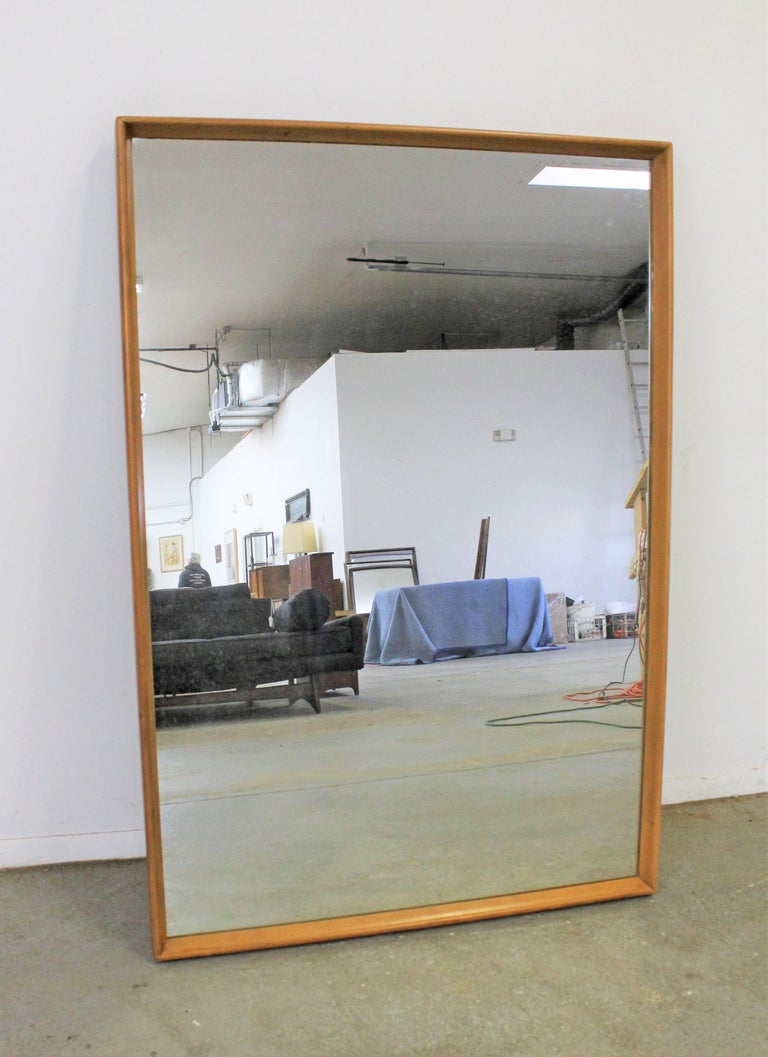 Offered is a large vintage Mid-Century Modern mirror by Heywood Wakefield. It has a wood frame with a Champagne finish. It is in good condition for its age, shows some age wear including minor imperfections on the glass and surface scratches/wear on