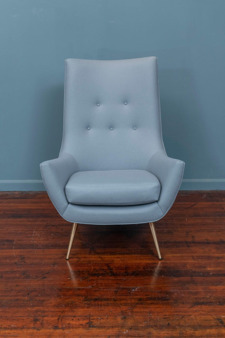Mid-Century Modern high back lounge chair newly upholstered on polished brass legs, ready to enjoy.
