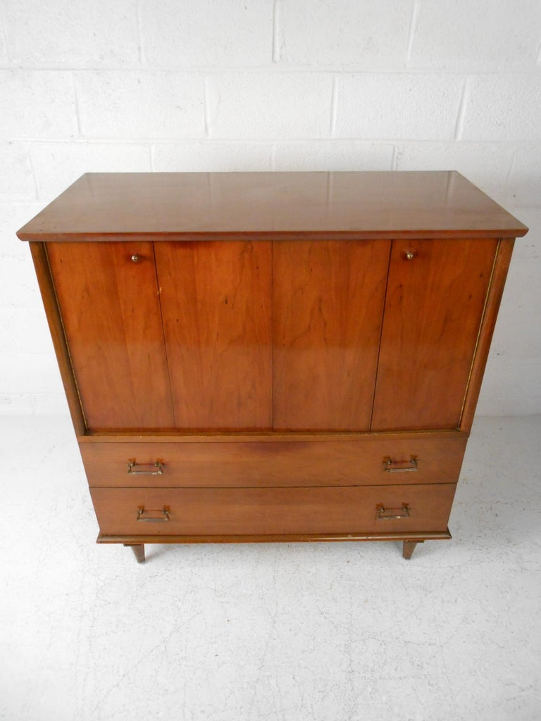 Mid-Century Highboy Dresser by Mengel Furniture Company. Sturdily constructed. Four drawers are concealed by two unusual hinged sliding cabinet doors, along with two additional drawers on the base which combine to ensure ample storage space.