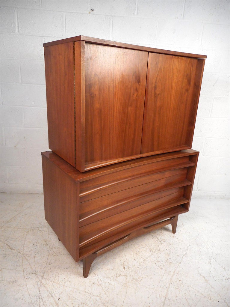 Stylish midcentury highboy dresser with a curved front. Handsome walnut veneer exterior, with a noteworthy book-matched grain pattern on the cabinet doors, which are mounted on sturdy piano hinges. Three spacious drawers on the piece's bottom