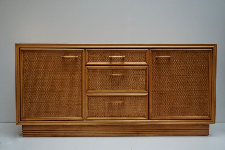 Fantastic 1950s-1960s Italian bamboo and rattan sideboard with three drawers and two side doors. The credenza features gorgeous woven rattan panels with bamboo frames. The case is raised on a decorative bamboo base. It offers ample storage, with