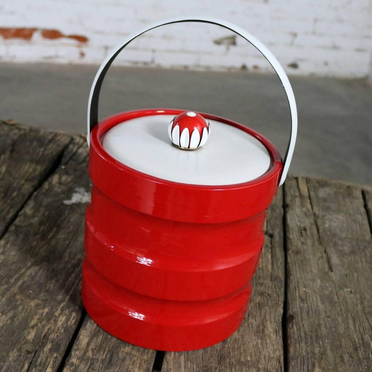 Fun vintage Mid-Century Modern red faux patent leather and white faux leather and plastic ribbed ice bucket with a mod red and white daisy knob. This fantastic ice bucket is in wonderful vintage condition, circa 1960s-1970s.  We just love this