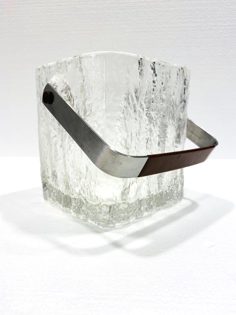Mid-Century Modern glass ice bucket with textured ice cube design. Vintage Japanese personal size ice bucket comprised of thick chunky glass with polished edges and translucent base. Features a stainless steel handle wrapped in brown stitched