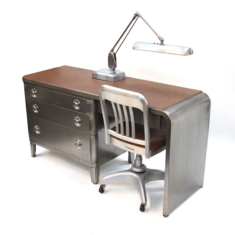 Three pieces of iconic mid-century industrial design combine to complete this fantastic home-office suite.  - Simmons dresser/desk (by renowned designer Norman Bel Geddes) - Goof Form desk chair - Dazor desk lamp All three pieces feature