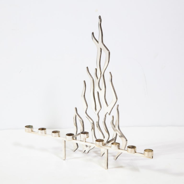 This stunning and graphic Mid-Century Modern Brutalist menorah was realized in Israel, circa 1960. Fabricated in silver plate, it features a candelabra stand composed of nine cylindrical candle holders (the center one appears raised via a