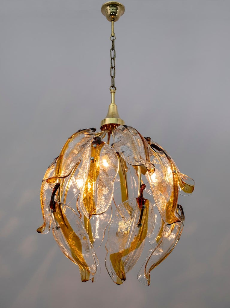 Chandelier composed of 15 large petals in transparent and amber Murano glass, with brass structure.