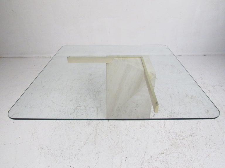 This wonderful vintage modern cocktail table features a unique travertine base with brass plated bars supporting a thick glass top. The geometric shaped base allows the glass top to appear as if it's floating on one side. An elegant Italian design