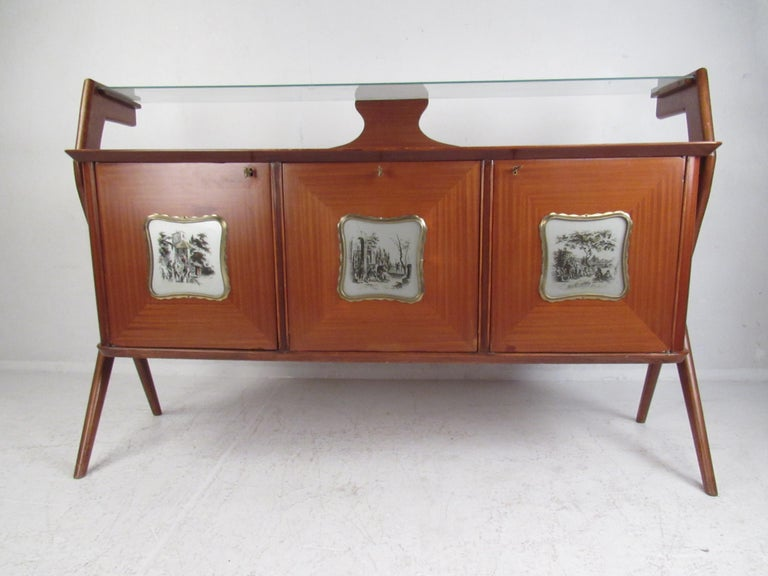 This stunning vintage modern sideboard features a floating glass top and angled legs. Sleek design with three decorative cabinet doors that depict old fashioned European scenery painted on glass fixtures. Lovely vintage finish with elegant wood