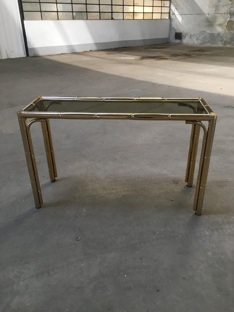 Mid-Century Modern Italian gilt finished faux bamboo console with smoked glass top. This console could become a set together with its gilt finished faux bamboo framed mirror and one gilt finished faux bamboo étagère with glass shelves (see photo