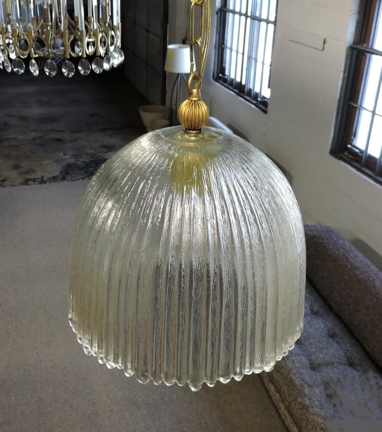 Beautiful Italian glass pendant lamp. This light has a heavy, ribbed and textured dome shade with an uneven edge.