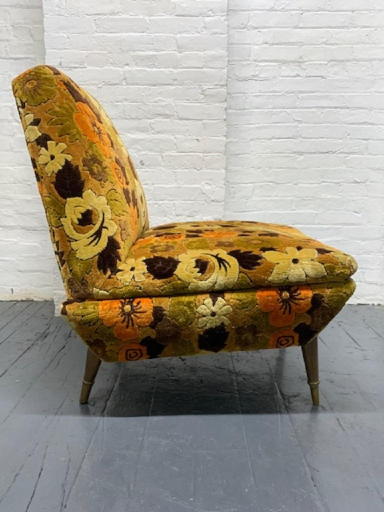 Mid-Century Modern Italian lounge chair armless lounge chair with original floral upholstery. Has wood legs with brass sabots.